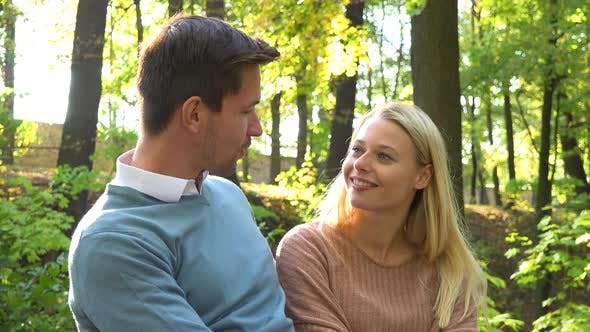 Thumbnail for A Young Attractive Couple Hugs and Talks on a Bench in a Park on a Sunny Day, Closeup
