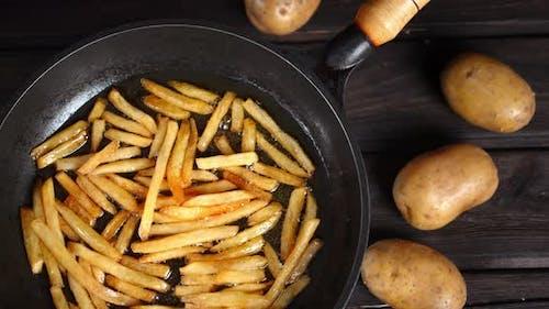 Pommes Frites in Öl in einer Bratpfanne gebraten.