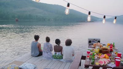 Friends Sitting on Wooden Pier at Lake Party
