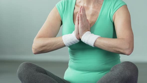 Thumbnail for Senior Female Sitting in Lotus Position, Putting Palms Together, Doing Yoga