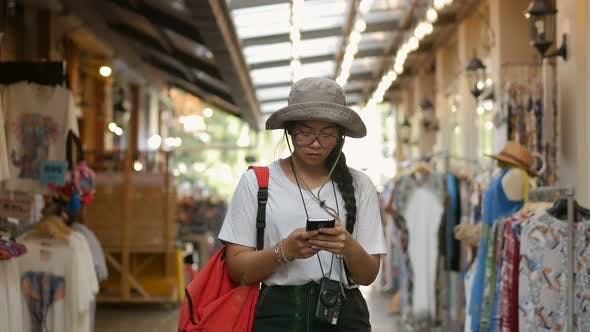 Young Asian woman hand using smartphone at the market.