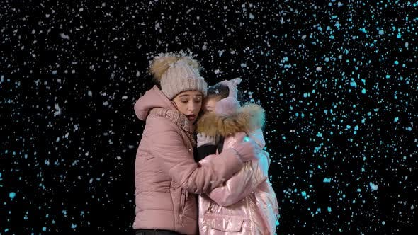 Mom and Child Froze and Hug To Keep Warm. A Woman and a Little Girl in Warm Winter Clothes on the