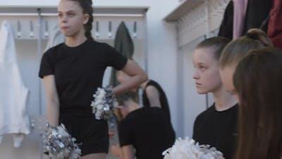 Girls Practicing Cheerleading Routine in Locker Room