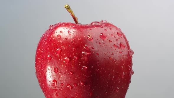 Thumbnail for Red apple with water droplets on it slowly rotating