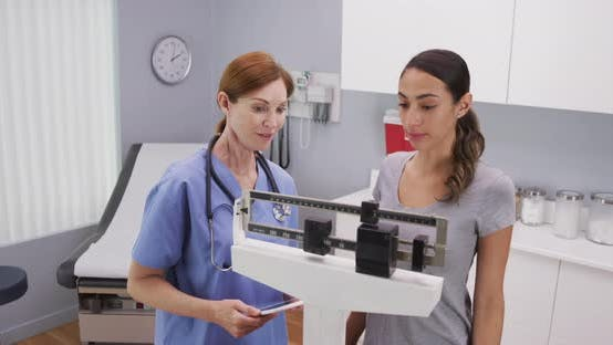 Thumbnail for Mid aged caucasian nurse weighing female patient on scale