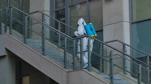 Disinfector in a Protective Suit Treats the Territory of City Streets, Sprays an Antibacterial