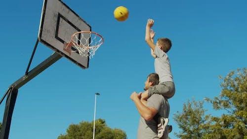 Vater und Sohn spielen Basketball auf der Straße und werfen einen Ball in den Korb.