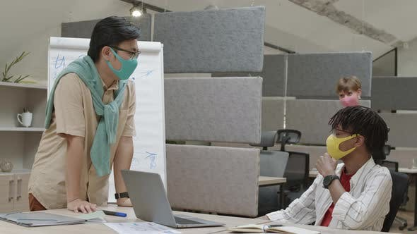 Female Manager Greeting Coworkers in Office