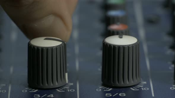 Thumbnail for Male Fingers Turning Knobs on Audio Mixing Desk