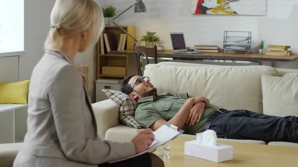 Cover Image for Young Arab Patient Lying on Couch and Talking to Female Psychotherapist