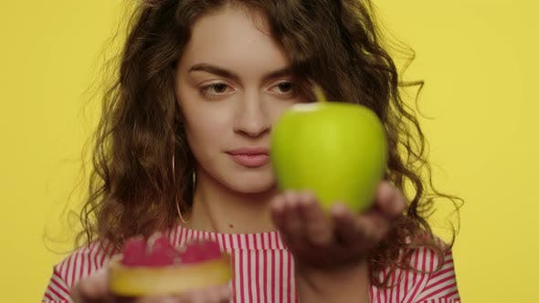 Thumbnail for Young Woman Weighing Apple and Cake in Hands in Yellow Studio