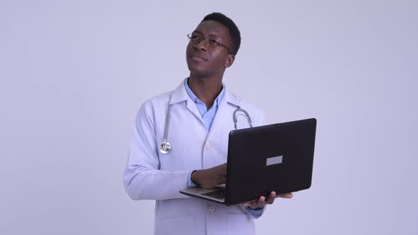 Thumbnail for Young Happy African Man Doctor Thinking While Using Laptop