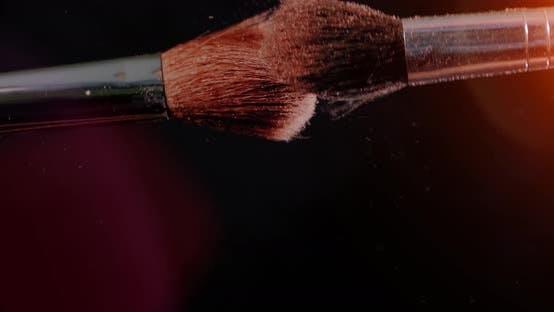 Thumbnail for Zwei Make-up-Pinsel mit Puder auf schwarzem Hintergrund mit Sonnenlicht Farbe Paint Konzept Zeitlupe