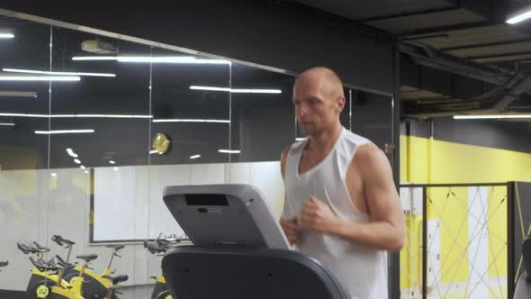 Thumbnail for Caucasian young man in sportswear running on treadmill at gym. Fitness, bodybuilding