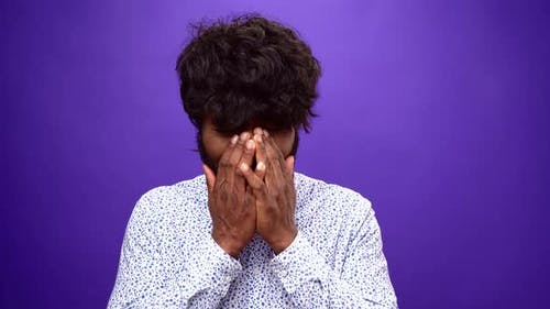 Upset African American Man Starts Crying Closing Face with Hands Purple Background