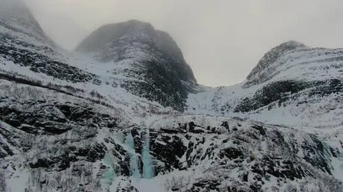 Aerial view of a mountain in Lyngen Alps with frozen waterfalls, Norway, Arctic