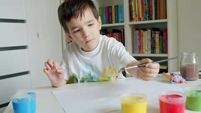 Boy Reaching for Paints With Paintbrush and Painting