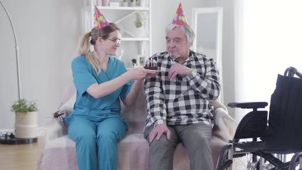 Thumbnail for Kind Caucasian Woman Giving Birthday Cake To Old Grey-haired Man in Nursing Home. Depressed Retiree
