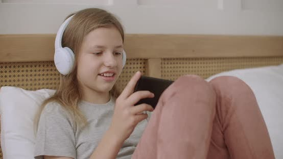 Thumbnail for Teen Girl Is Playing Internet Games in Cellphone at Home, Lying in Bedroom in Sunday Morning and