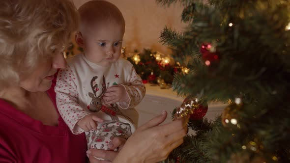 Grandmother with Her Granddaughter at the Christmas Tree