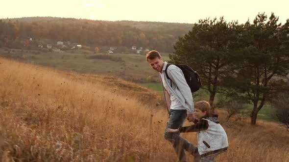 Walk In The Nature Of Dad And Son. Dad And Son Climb The Hill.