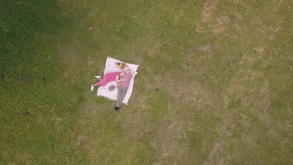 Thumbnail for Family Weekend Picnic in Park. Aerial View. Senior Old Couple Lie on Blanket on Green Grass Meadow