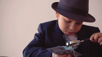 Child Boy Looks Like a Businessman in Hat and Suit is Looking at Dollars with Magnifier