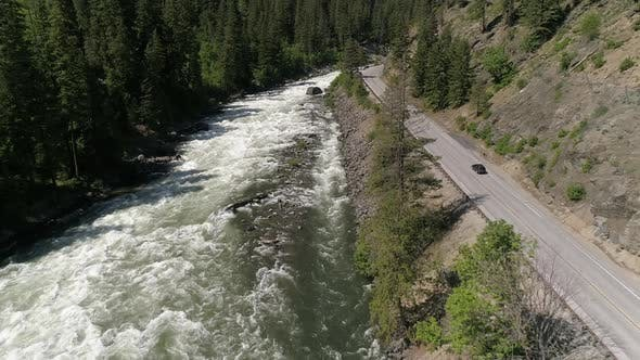 Thumbnail for Drone Following Car On Roadtrip Traveling Mountain Road By Scenic Canyon River