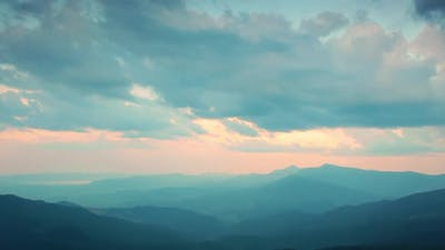 Sunset and Clouds Over the Silhouettes of the Mountains