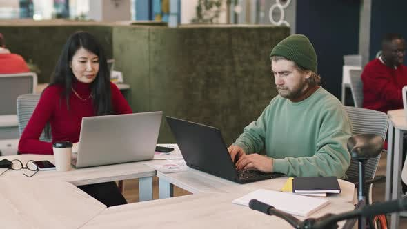 Businesspeople Working on Laptops in Coworking Space