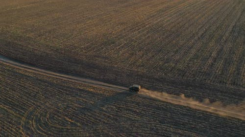 Aerial Shot of Farmer Jeep Riding Through Empty Rural Road Among Field. Off Road Vehicle Speeding on