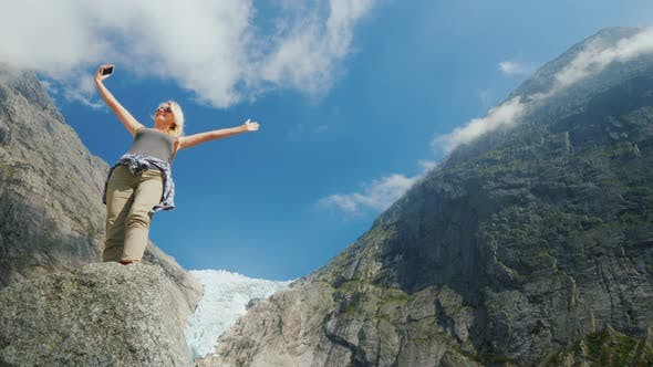 Cover Image for A Successful Young Woman Photographes Herself Against the Backdrop of Mountains and a Glacier in