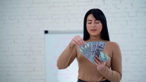 Thumbnail for Woman holding money banknotes. Portrait of a cheerful young woman holding money banknotes