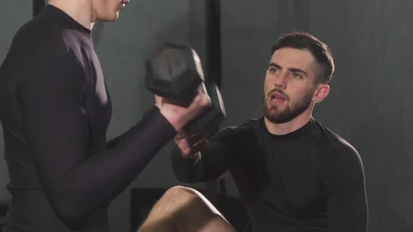 Thumbnail for Handsome Bearded Male Personal Trainer Helping Young Man at the Gym