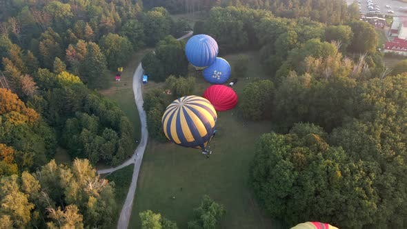 Aerial View of Hot Air Balloons Prepare for an Summer Early Morning Flying in Park in Small European