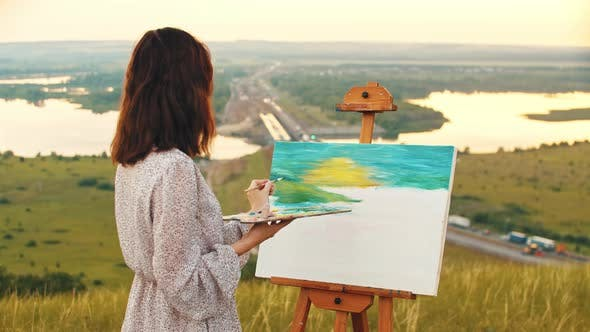 Young Woman Drawing a Painting Inspired By the Sunset