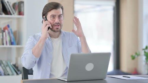 Wütender Mann mit Laptop, der auf dem Smartphone spricht