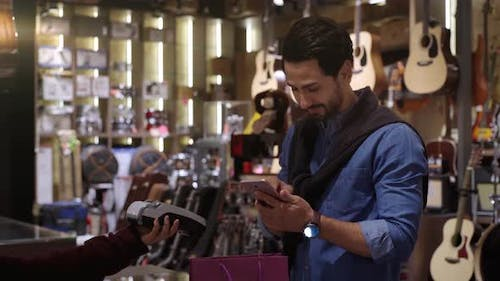 A Middle Eastern Man Using Mobile Phone To Purchase Product