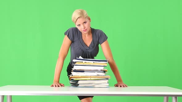 Thumbnail for Portrait of very stressed businesswoman overwhelmed with large pile of work