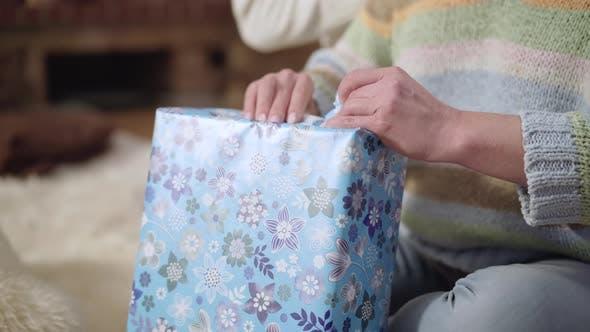 Weibliche kaukasische Hände, die Weihnachtsgeschenk drinnen auspacken