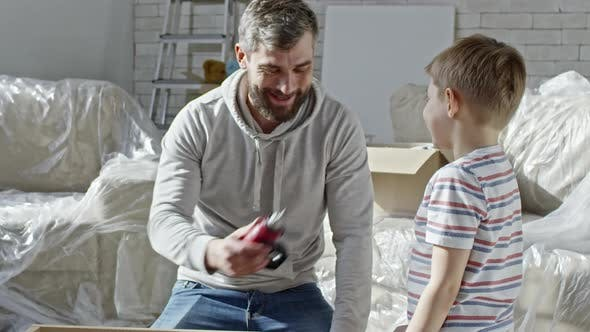 Thumbnail for Boy Watching Father Assembling Furniture
