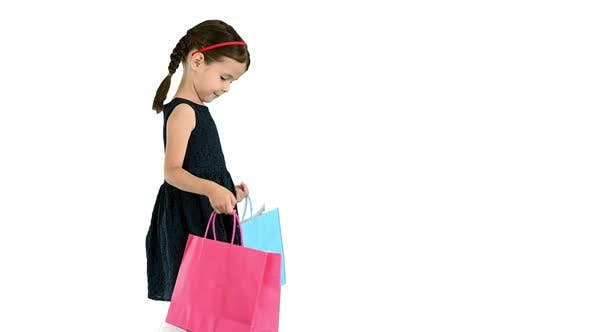 Thumbnail for Beautiful Little Girl in Black Dress Walking with Shopping Bags on White Background