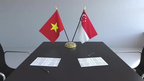 Flags of Vietnam and Singapore and Papers on the Table