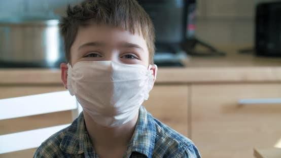Kleiner Junge in Quarantäne zu Hause Blick auf die Kamera in blaue medizinische Maske