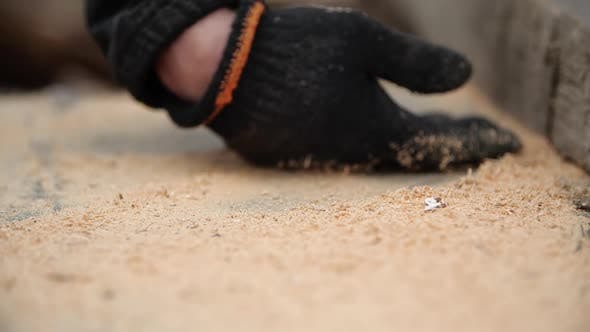 Thumbnail for Man's Hand in Working Glove Crushes Sawdust From Table Into Chamber After Sawing Board with Circular