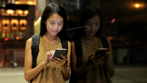 Cover Image for Woman use of smart phone in city at night