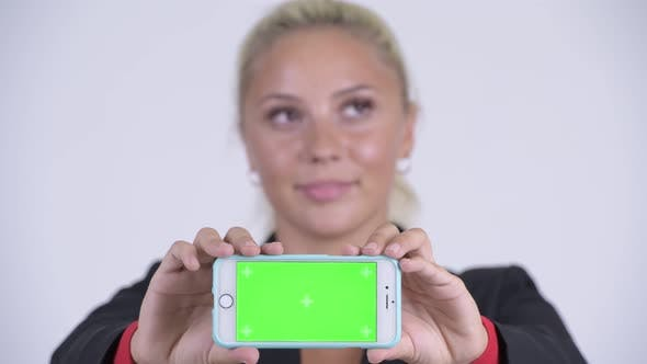 Cover Image for Face of Young Happy Blonde Businesswoman Thinking and Showing Phone