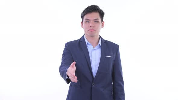 Thumbnail for Happy Young Asian Businessman Giving Handshake
