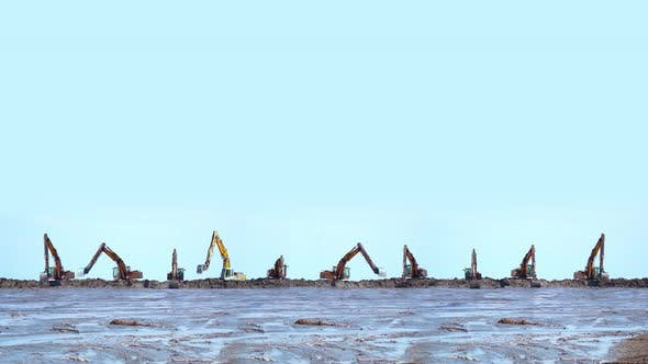 Many Excavators Dig the Wet Sand