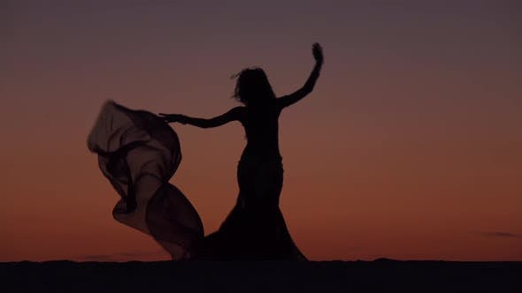 Thumbnail for Dancer Holds a Veil in Her Hands, She Dances a Belly Dance on the Beach. Silhouette